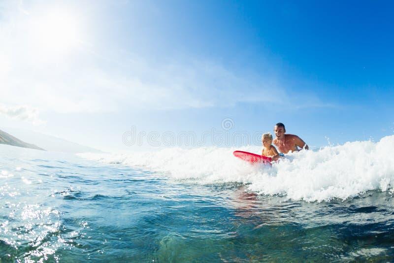 一起冲浪的父亲和的儿子,乘坐的波浪 免版税图库摄影