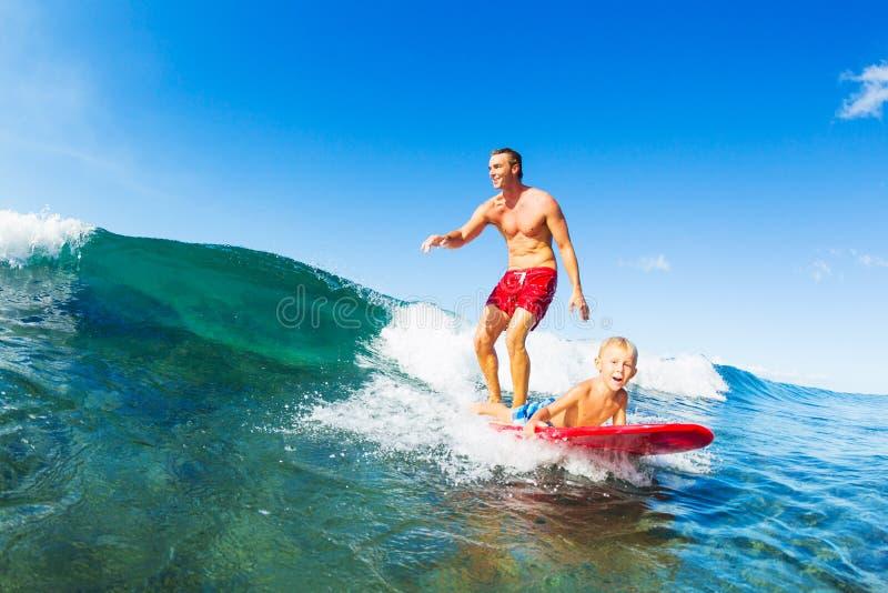 一起冲浪的父亲和的儿子,乘坐的波浪 免版税库存图片