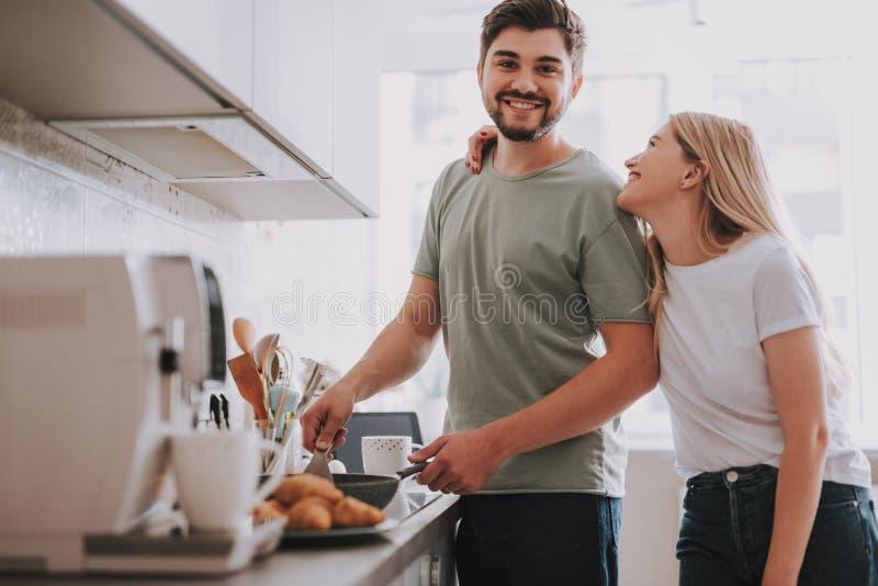 一起准备早餐的愉快的年轻夫妇在轻的内部 免版税库存照片