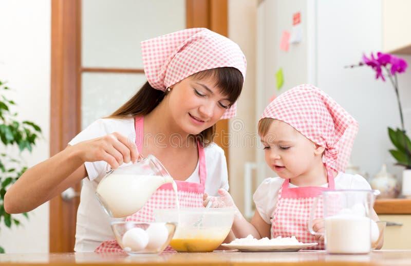 一起准备曲奇饼的母亲和孩子在厨房 免版税库存图片