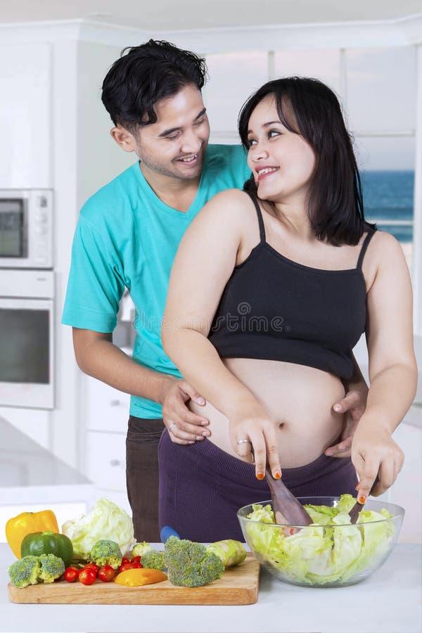 一起准备沙拉的愉快的夫妇 图库摄影