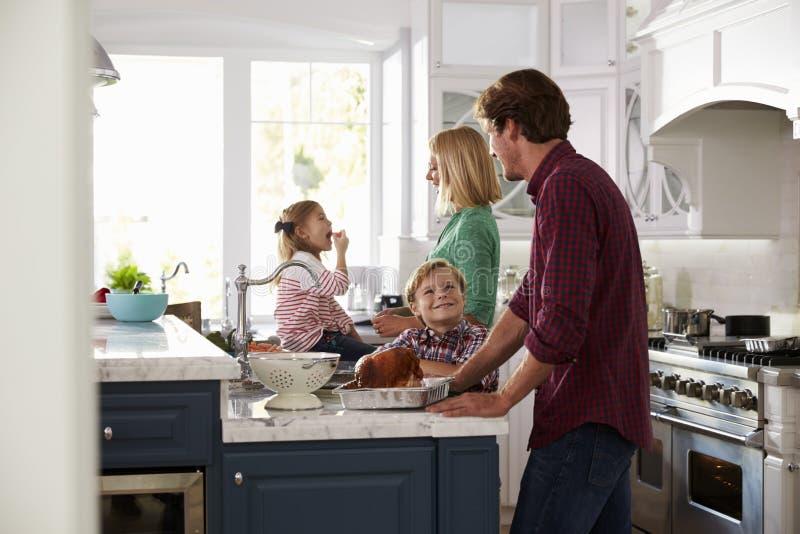 一起准备烘烤土耳其膳食的家庭在厨房里 库存图片