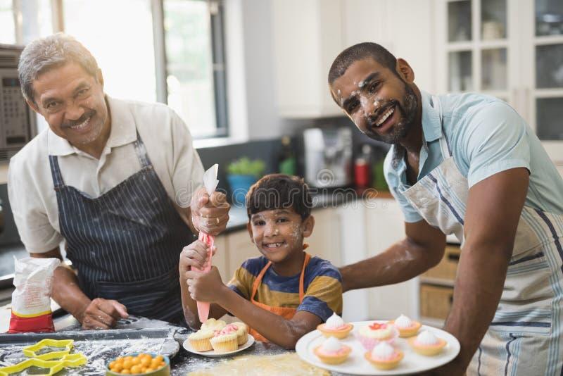 一起准备甜食物的愉快的多代的家庭画象在厨房里 免版税图库摄影