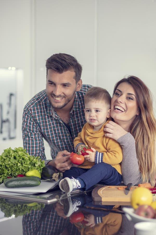 一起准备菜的愉快的家庭在家在厨房里 免版税图库摄影