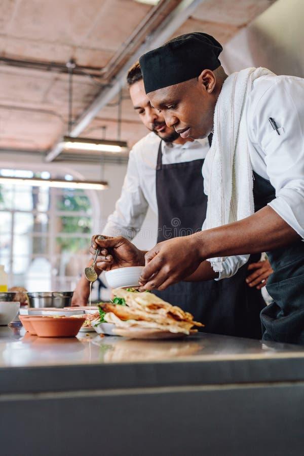 一起准备食物的厨师在餐馆厨房里 免版税库存图片