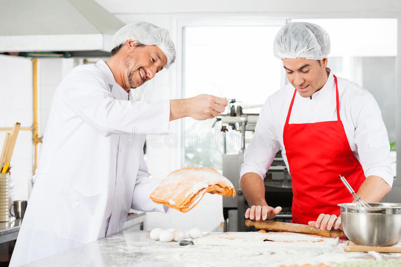 一起准备馄饨面团的微笑的厨师  免版税库存照片