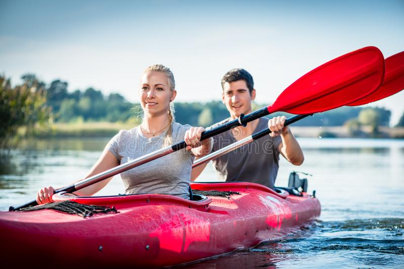 一起划皮船在湖的夫妇 免版税库存照片