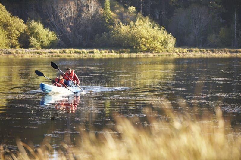 一起划皮船在湖,正面图的父亲和儿子 免版税库存图片