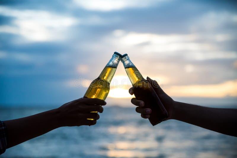 一起叮当响瓶啤酒的两个人剪影  免版税图库摄影