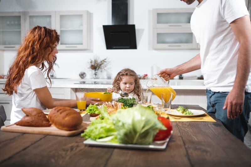 一起吃在厨房里的快乐的家庭 免版税库存图片