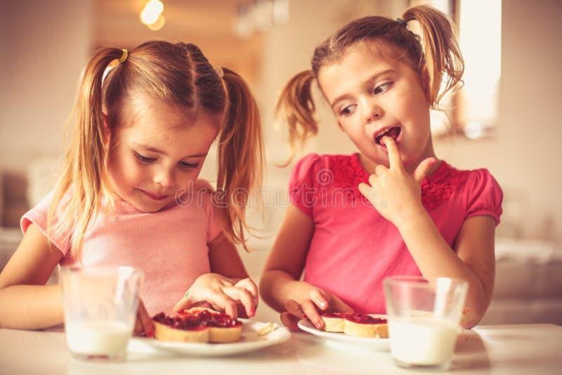 一起吃家庭早餐的妹 库存图片