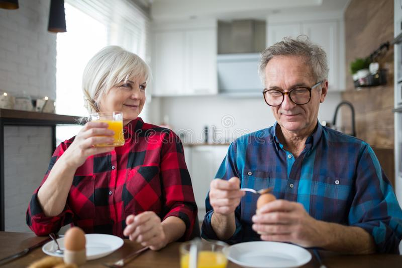 一起吃早餐的愉快的资深夫妇 免版税图库摄影