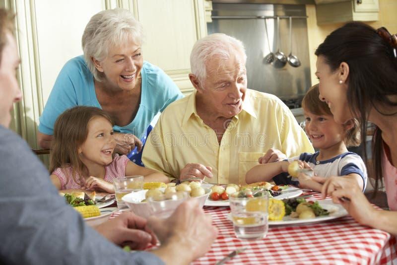 一起吃膳食的多一代家庭在厨房里 免版税图库摄影