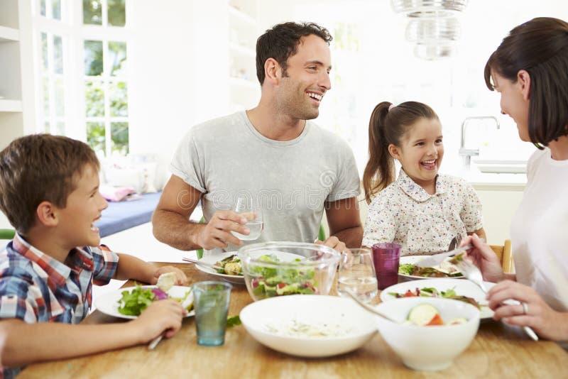 一起吃膳食的家庭在厨房用桌附近 免版税库存照片