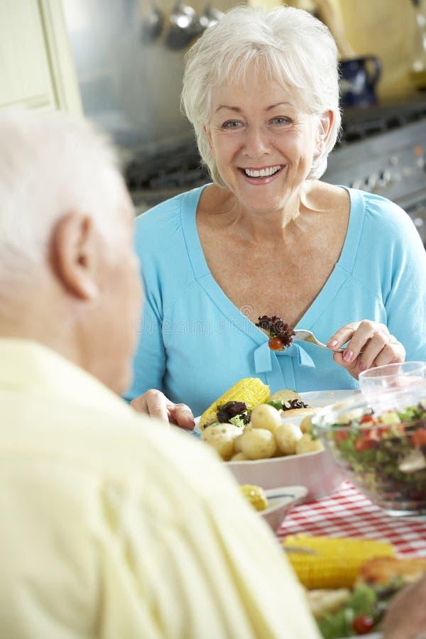 一起吃膳食的资深夫妇在厨房里 免版税库存图片