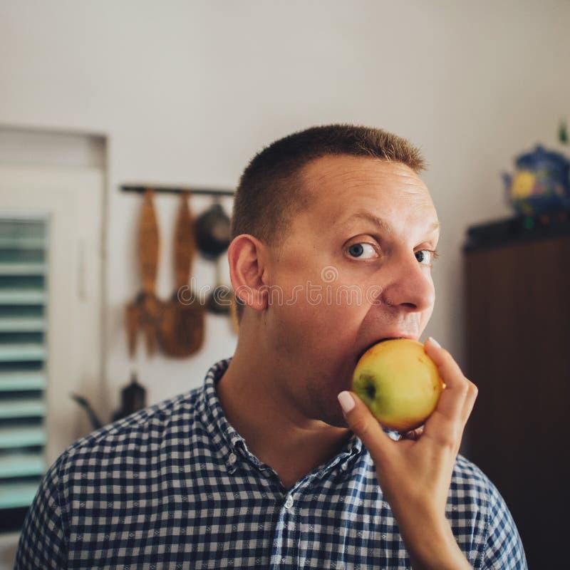 一起吃苹果的美好的年轻夫妇在厨房里 库存图片