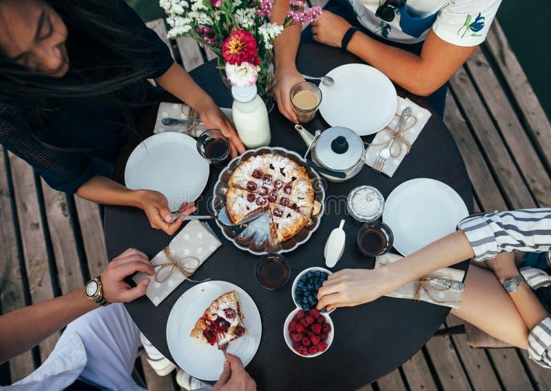 一起吃饼的愉快的朋友顶视图  免版税库存图片