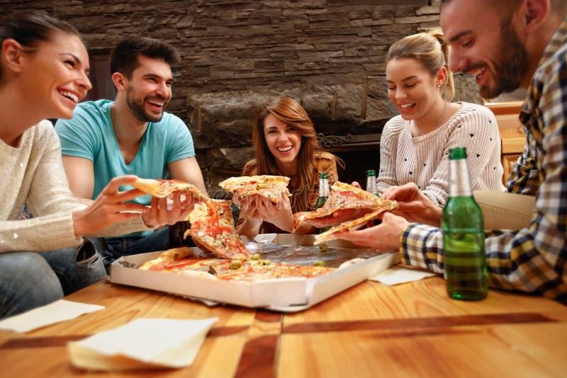 一起吃` s大薄饼的小组青年人 图库摄影