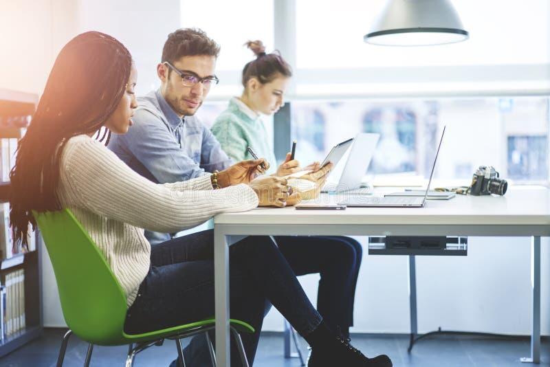 一起合作在现代明亮的办公室的小组工友 免版税库存照片