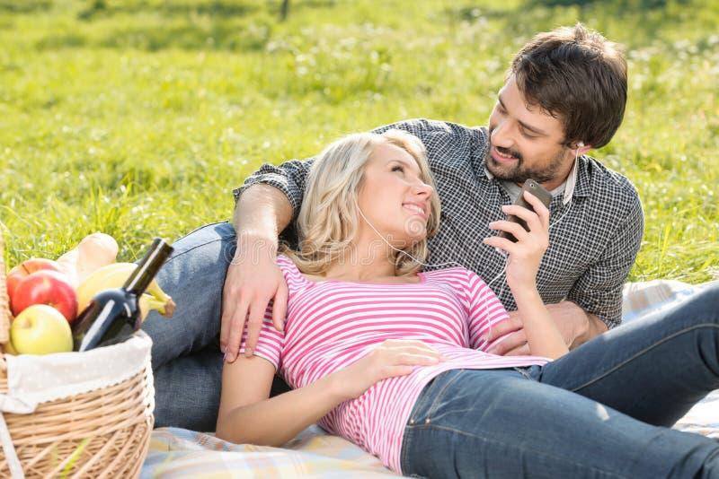 一起听到音乐。爱恋的年轻夫妇听的t 库存图片
