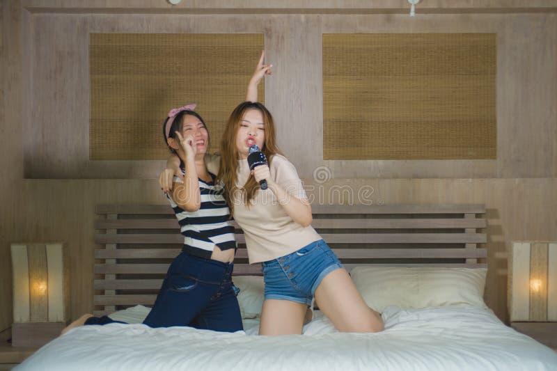 一起唱与话筒和手机的年轻愉快和激动的亚裔韩国女孩网上卡拉OK演唱歌曲在家跳跃 库存照片