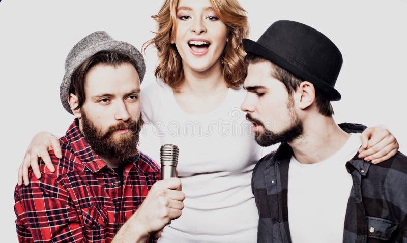 一起唱卡拉OK演唱的愉快的朋友在白色背景 关闭 库存图片