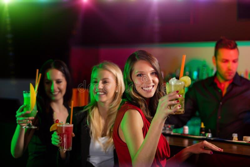 一起喝鸡尾酒的年轻朋友在党 库存照片