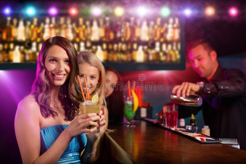 一起喝鸡尾酒的年轻朋友在党 免版税库存照片