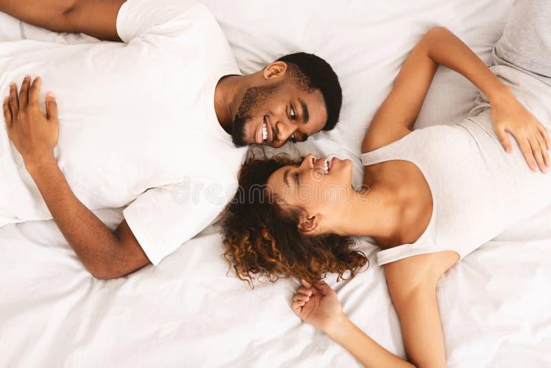 一起在床上和看照相机的年轻爱恋的夫妇 库存图片