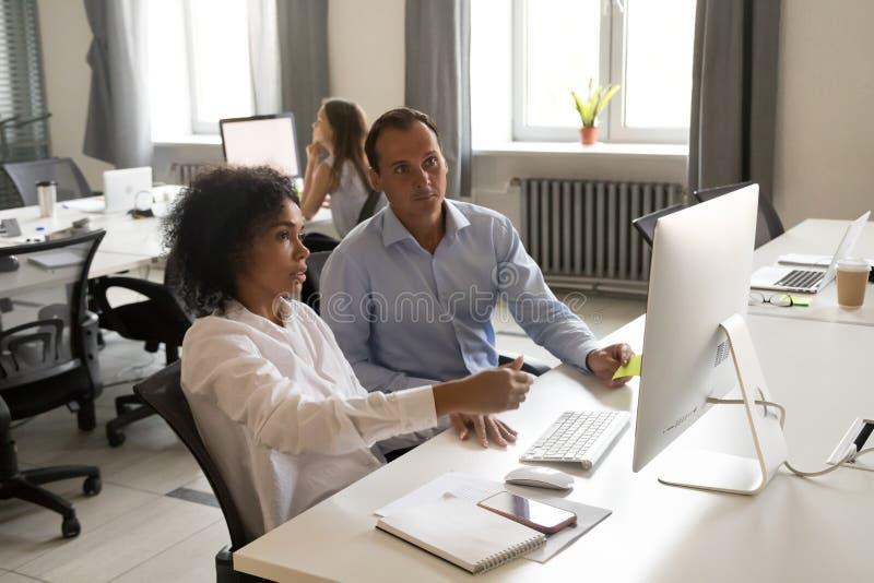 一起在网上谈论不同的同事他们的工作 免版税库存图片