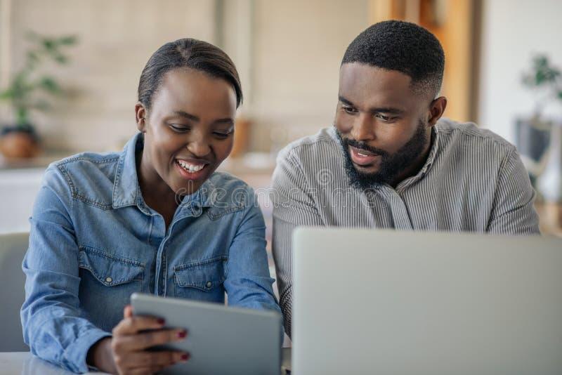 一起在网上运作微笑的年轻非裔美国人的夫妇在家 库存图片