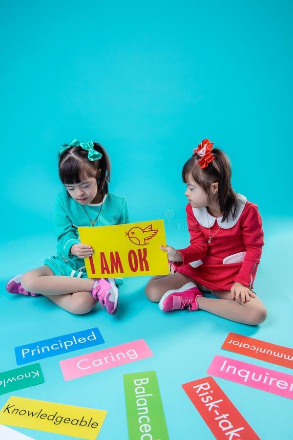 一起坐两个的妹和运载的海报 免版税图库摄影