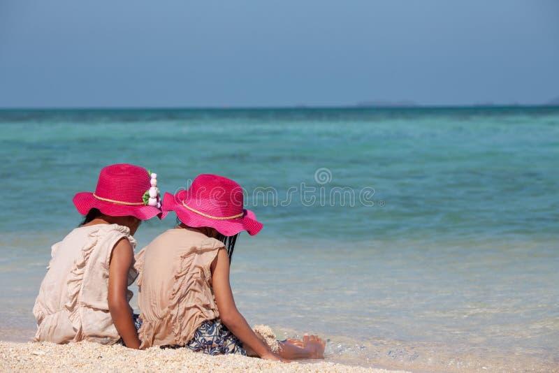 一起坐和使用与沙子的两个逗人喜爱的亚裔小孩女孩在海滩在美丽的海附近 库存照片