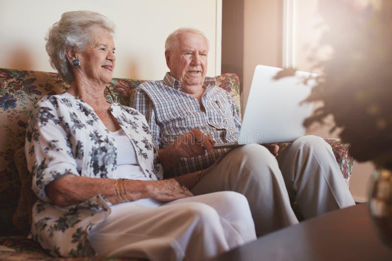 一起坐和使用膝上型计算机的资深夫妇 免版税库存图片