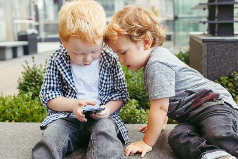 一起坐和打比赛的白种人小孩男孩在细胞手机数字式片剂 免版税图库摄影
