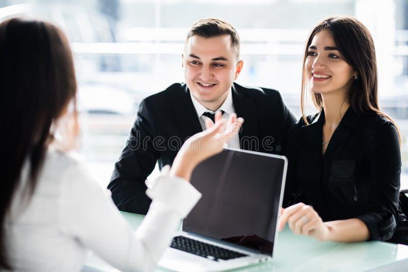 一起坐在书桌和听他们的财政顾问的年轻夫妇 库存图片