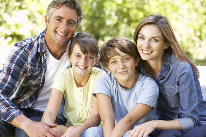一起坐在庭院里的愉快的家庭画象 免版税库存图片