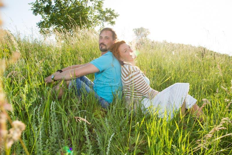 一起坐在户外野餐的愉快的有吸引力的夫妇 在草的夫妇在绿草的夏天森林里 免版税库存照片