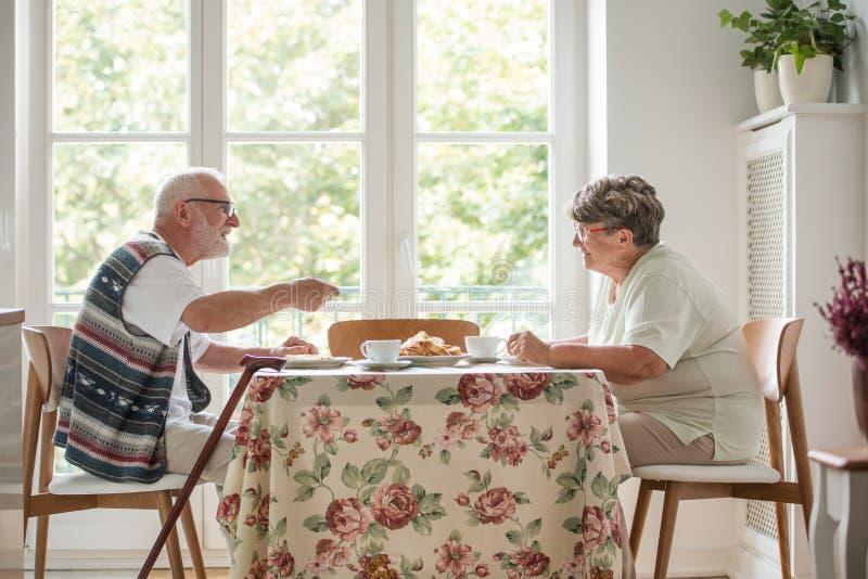 一起坐在桌饮用的茶和吃蛋糕的资深夫妇 库存照片
