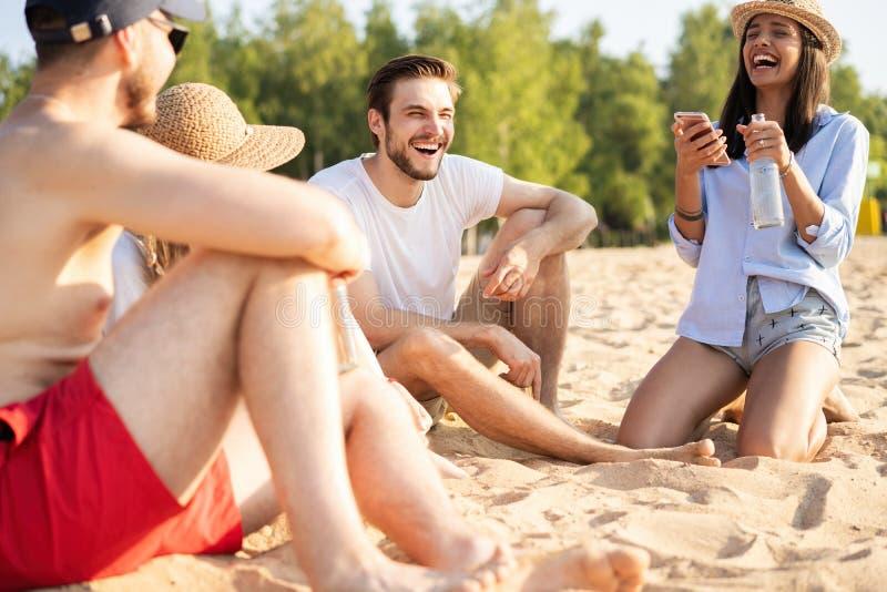 一起坐在海滩谈的和饮用的啤酒的小组愉快的年轻人 免版税图库摄影