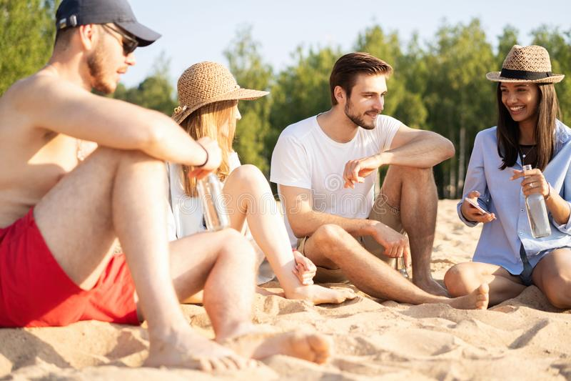 一起坐在海滩谈的和饮用的啤酒的小组愉快的年轻人 库存图片