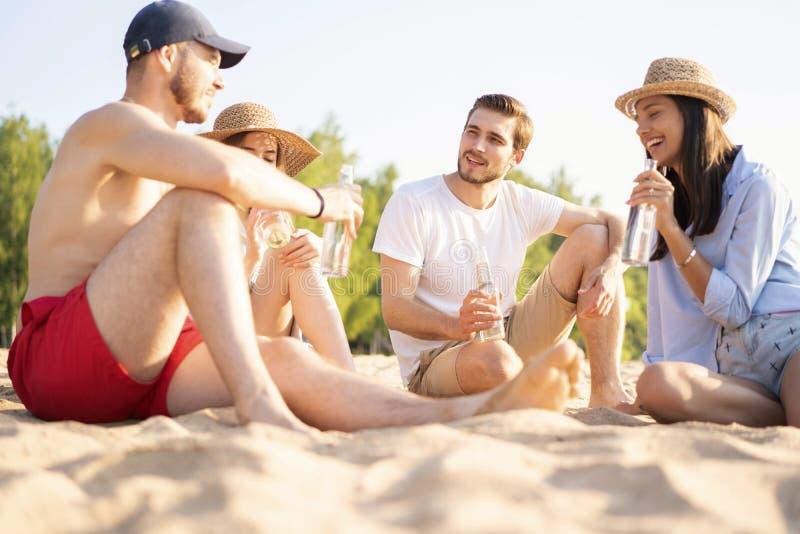 一起坐在海滩谈的和饮用的啤酒的小组愉快的年轻人 图库摄影