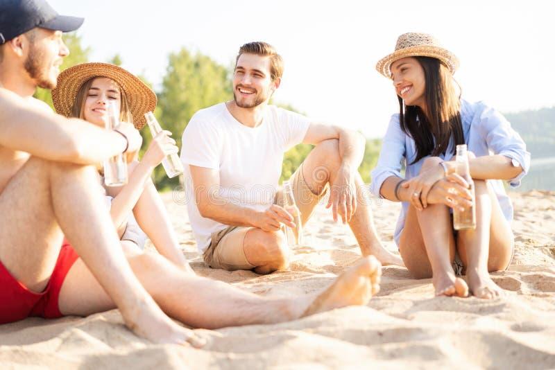 一起坐在海滩谈的和饮用的啤酒的小组愉快的年轻人 免版税库存照片