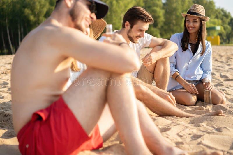 一起坐在海滩谈的和饮用的啤酒的小组愉快的年轻人 免版税库存图片