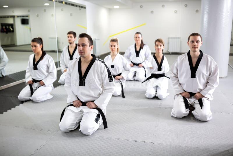 一起坐在跆拳道锻炼以后的小组老练的军事艺术家和巴拉军事艺术家 库存图片