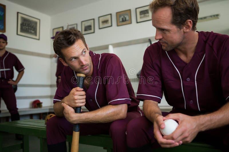 一起坐在更衣室的棒球运动员 库存图片