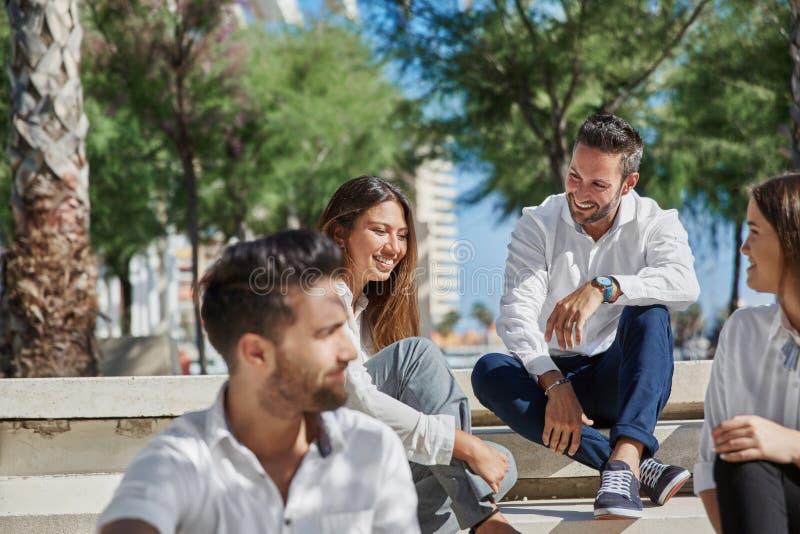 一起坐外部笑的年轻愉快的人民 免版税库存照片
