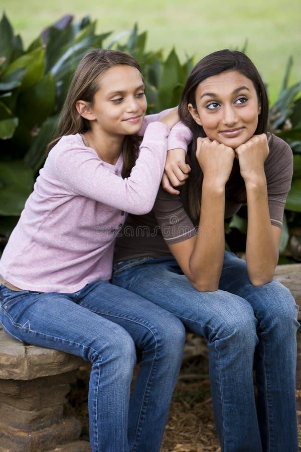 一起坐富感情的长凳的姐妹 免版税库存照片
