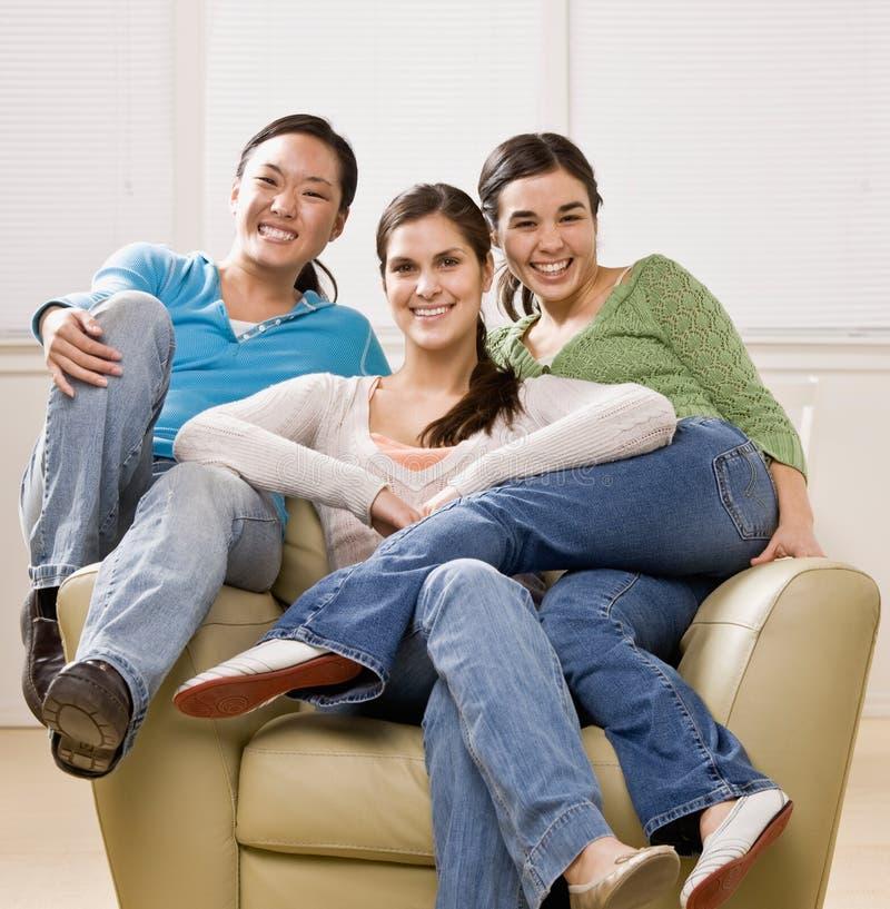 一起坐扶手椅子的朋友 免版税图库摄影