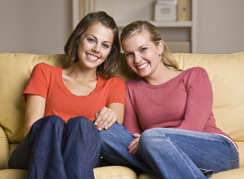 一起坐沙发的朋友 库存图片